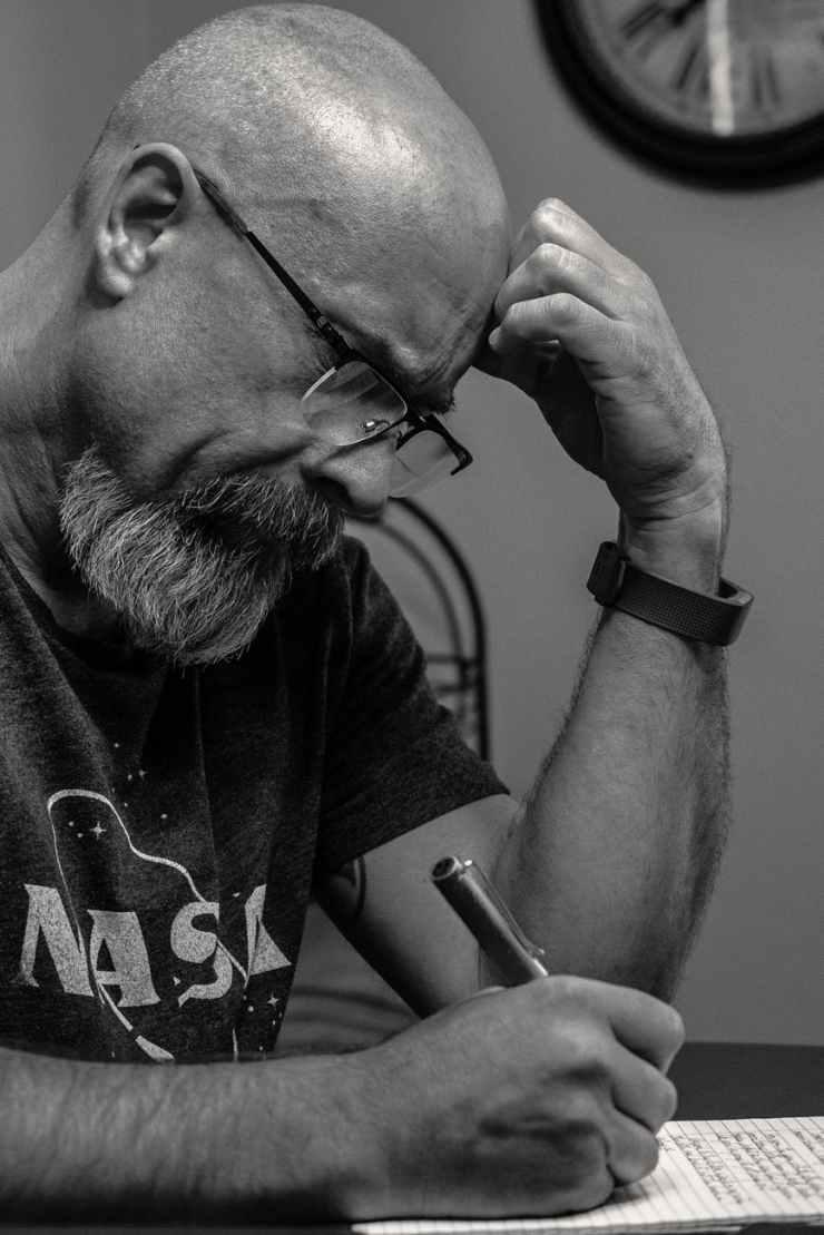 man holding pen grayscale photo